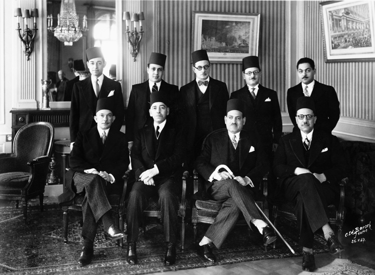 A photo representing the kaleidoscope that was Egypt in May 1937; the bipartisan multi-ethnic Egyptian delegation to the League of Nations pauses for a photo-op at Geneva's Hotel des Bergues: Seated from L-R: Ali Chamsi Pasha (Muslim), Foreign Minister Wassef Ghali Pasha (Copt), Prime Minister Mustafa Nahas Pasha (Muslim) and Wafd Party elder William Makram-Ebeid Pasha (Copt). Photo From http://www.indiana.edu/~league/photocategories.htm